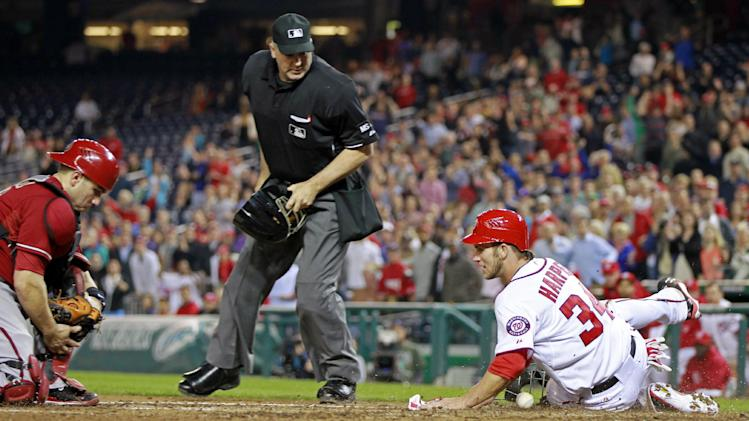 Washington Nationals' Bryce Harper (34) slides across home plate as Arizona Diamondbacks catcher Miguel Montero loses the ball during the fourth inning of a baseball game, Wednesday, May 2, 2012, in Washington. At center is home plate umpire Bill Welke. (AP Photo/Haraz N. Ghanbari)