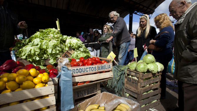 In this photo taken Wednesday Aug. 31, 2011, people buy fruit and vegetables at the Central Market in Buenos Aires, Argentina.  While the U.S. and Europe struggle to revive their economies by imposing austerity measures, South American leaders have generally done the opposite, spending their way to growth and the voters' acclaim.  Argentina's President Cristina Fernandez raised what was already the highest minimum wage south of the U.S. border by another 25 percent in September 2011.  (AP Photo/Victor R. Caivano)