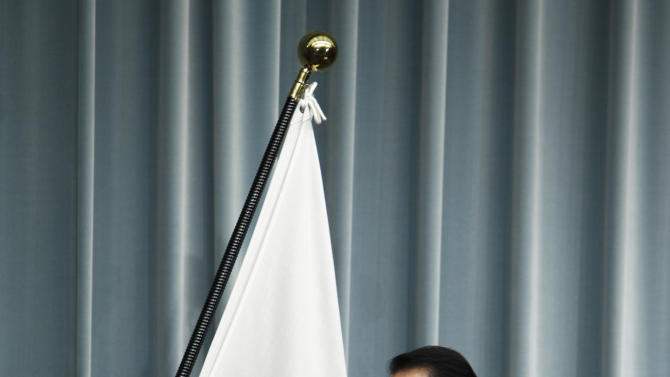 Japanese Prime Minister Naoto Kan pauses near the national flag as he arrives for a press conference at his official residence in Tokyo, Wednesday, July 13, 2011. Kan said he wants the country to learn from its ongoing crisis and become less reliant on nuclear energy. He said the risk of nuclear energy is too high and he wants to wean the nation off nuclear and eventually seek a society that can do without it. (AP Photo/Shizuo Kambayashi)