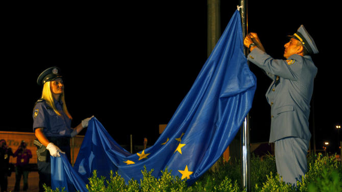 A Croatian police officer, left, and a customs officer raise a European Union flag at the border crossing between Croatia and Slovenia during celebrations marking Croatia's EU accession, in Bregana, early Monday, July 1, 2013. Croatia has become the 28th member of the European Union, a major milestone some 20 years after the small country won independence in a bloody civil war that shook the continent. (AP Photo/Nikola Solic)
