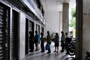 People queue at a national Bank of Greece ATM in central …