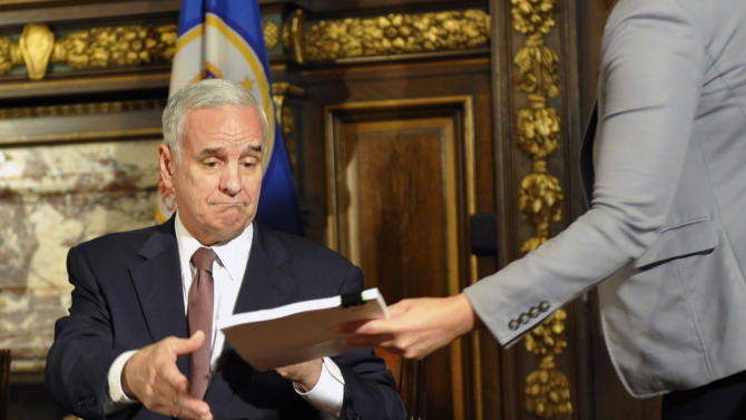 """Minnesota Gov. Mark Dayton is handed one of the bills as he signs the state budget bill which ends the government shutdown, Wednesday, July 20, 2011 in St. Paul, Minn. Dayton's signature came just hours after lawmakers gave their own approval to the deal after meeting in special session that started Tuesday afternoon and lasted until early Wednesday morning. After signing the budget, Dayton said he was """"not entirely happy"""" with it. (AP Photo/Jim Mone)"""