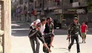 An image grab taken from AFPTV shows Syrian rebels carrying a wounded man after clashes in the Salaheddin district of Aleppo. Syrian regime warplanes pounded rebel positions in second city Aleppo on Sunday ahead of a threatened ground assault by more than 20,000 troops assembled around the commercial capital