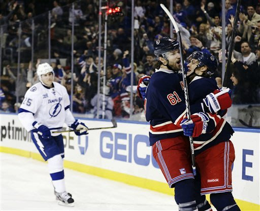 New York Rangers left wing Rick Nash (61) hugs Carl Hagelin (62) as Tampa Bay Lightning&#39;s Matt Carle (25) reacts after Hagelin scored a goal during the second period of an NHL hockey game, Sunday, Feb. 10, 2013, in New York. (AP Photo/Frank Franklin II)