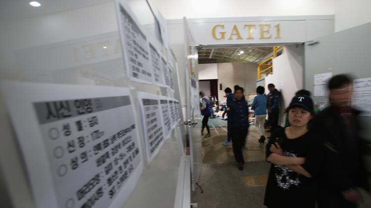 A family member of missing passengers onboard the South Korean ferry Sewol which capsized on Wednesday, looks at messages describing the look and dressing of a newly found body by rescue teams, at a makeshift accommodation hall in a gymnasium in Jindo