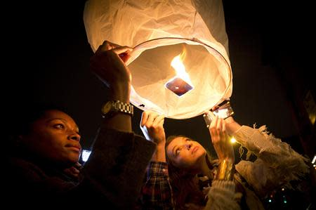 People release paper lanterns after lighting them outside a restaurant named in honor of former South African President Mandela, in the Brooklyn borough of New York