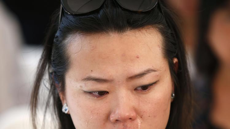 A woman cries as she watches a memorial service for murdered USC graduate student Ji Xinran on a television screen on the USC campus in Los Angeles