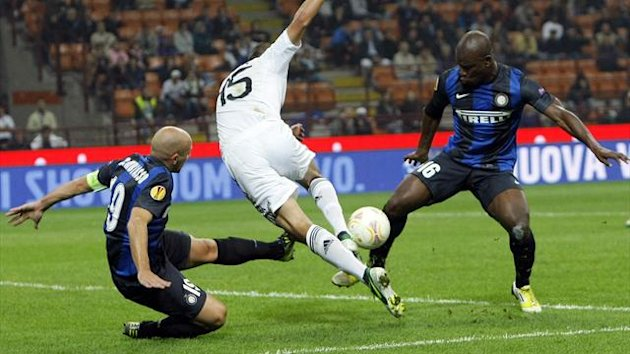 Inter Milan's Esteban Cambiasso (L) and Gaby Mudingayi (R) tackles Partizan Belgrade's Aleksandar Mitrovic during their Europa League Group H match at San Siro stadium in Milan (Reuters)