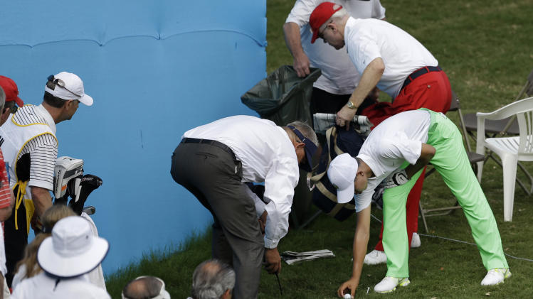 Amateur Guan Tianglang, 14, of China, has help from a marshal making his ball for a drop near the 16th green during the second round of the Byron Nelson Championship golf tournament Friday, May 17, 2013, in Irving, Texas. (AP Photo/Tony Gutierrez)