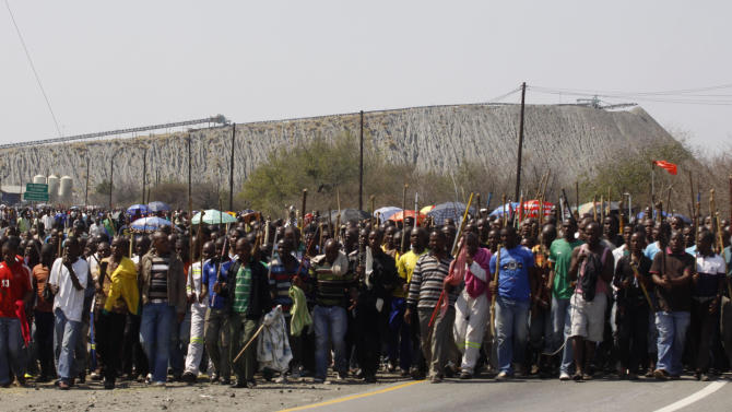 FILE-  Striking mine workers armed with machetes, sticks, and spears march to a smelter plant at the Lonmin Platinum Mine near Rustenburg, Wednesday, Sept, 12, 2012. Anglo American Platinum Ltd., the world's largest producer of the precious metal announced Monday Feb. 4, 2013 an operating loss of $715 million in 2012 due to violent labor unrest in South Africa. (AP Photo/Denis Farrell, file)
