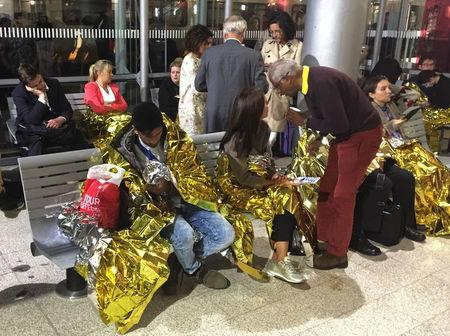 Passengers wrapped in thermal foil blankets given out by emergency services after their Eurostar train was stranded at Calais Station, after intruders were seen near the Eurotunnel, in Calais