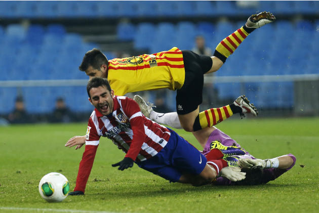 Sant Andreu's goalkeeper Pau Nunez, left, commits a penalty foul on Atletico's Adrian Lopez, right, during a Copa del Rey soccer match between Atletico de Madrid and Sant Andreu at the Vicente