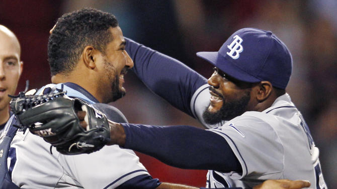 Tampa Bay Rays relief pitcher Fernando Rodney, right, smiles as he embraces catcher Jose Molina after earning a save in the Rays' 7-4 win over the Boston Red Sox in a baseball game at Fenway Park in Boston, Friday, May 25, 2012. (AP Photo/Charles Krupa)