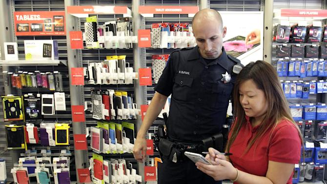 In this Nov. 12, 2012, photo, Sacramento Police Officer Matthew McPhail looks over a list of stolen merchandise with manager Katie Vang following an overnight break-in at a Radio Shack store in Sacramento, Calif. Sacramento voters, who don't want to see a reduction in service such as public safety, approved a sales tax hike by a 2-to-1 ratio. During last week's elections, voters across the country opted to raise taxes to help their cities, counties and school districts. (AP Photo/Rich Pedroncelli)