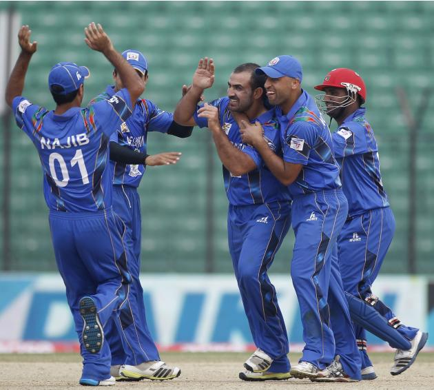 Afghanistan's fielders congratulate bowler Shenwari as he dismissed Pakistan's Maqsood successfully during their Asia Cup 2014 ODI cricket match in Fatullah