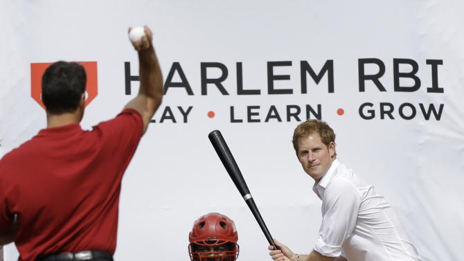 New York Yankees first baseman Mark Teixeira, left, pitches to Britain's Prince Harry during a visit to launch a partnership between Harlem RBI  and the Royal Foundation of the Duke and Duchess of Cambridge and Prince Harry in New York, Tuesday, May 14, 2013.  (AP Photo/Kathy Willens)