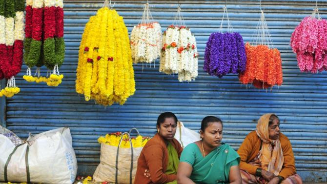 Vendors selling flower garlands on a pavement wait for customers outside a flower market in Bangalore