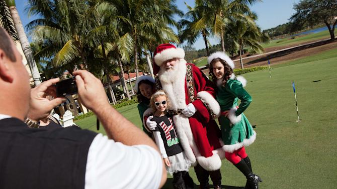 """Justin Einstein, left, takes a photo of his daughter, Brooke, 8, with Santa Claus and his elves during the Macy's National Santa Tour at the The Ritz Carlton Golf Resort in Naples, Fla., Friday, Dec. 21, 2012. Santa made the stop at the resort to see ten Make-A-Wish children and their families as part of the Macy's national tour. Now in its fifth year, Macy's """"Believe campaign invites children to mail letter to Santa using Macy's Santa Mail letterboxes. Macy's donates a dollar for each letter mailed in store up to $1 million, to Make_A-Wish. (Erik Kellar/AP Images for Macy's)"""