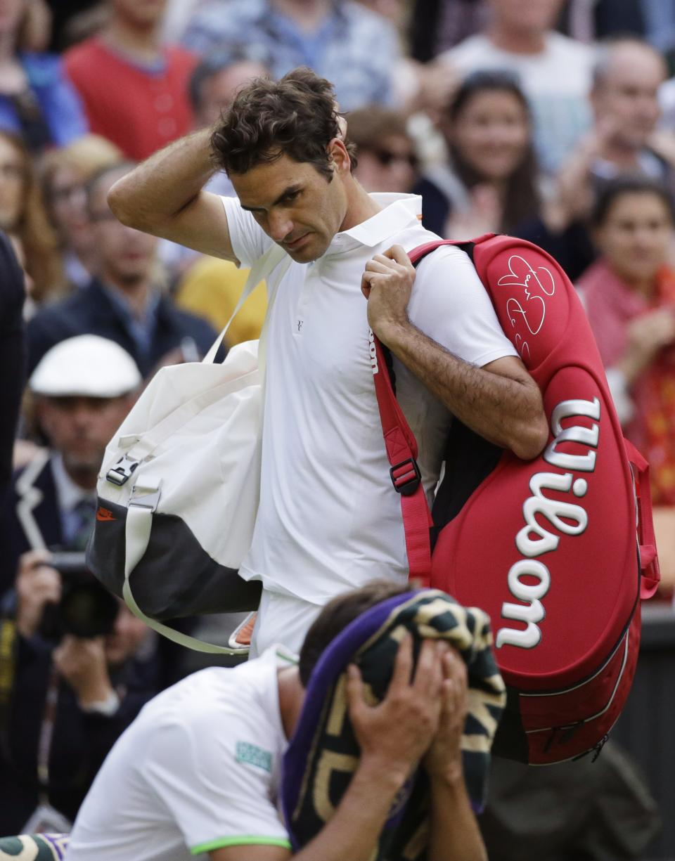 Roger Federer of Switzerland, back, looks to Sergiy Stakhovsky of Ukraine after he lost in their Men's second round singles match at the All England Lawn Tennis Championships in Wimbledon, London, Wednesday, June 26, 2013. (AP Photo/Anja Niedringhaus)