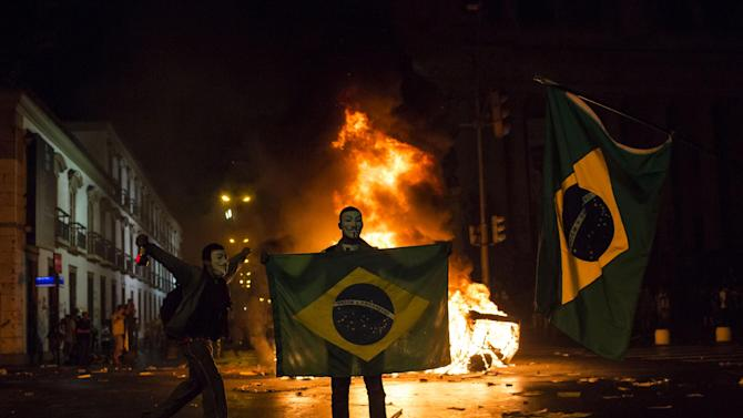 FILE - This June 17, 2013 photo, a demonstrator holds a Brazilian flag in front of a burning barricade during a protest in Rio de Janeiro in Rio de Janeiro, Brazil. Protesters massed in at least seven Brazilian cities for another round of demonstrations voicing disgruntlement about life in the country, raising questions about security during big events like the current Confederations Cup and a papal visit next month. (AP Photo/Felipe Dana, File)
