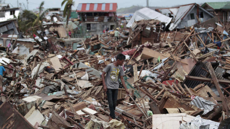 A Filipino man walks among debris from damaged homes at typhoon-hit Tacloban city, Leyte province, central Philippines on Wednesday, Nov. 13, 2013. Typhoon Haiyan, one of the strongest storms on record, slammed into six central Philippine islands on Friday leaving a wide swath of destruction. (AP Photo/Aaron Favila)