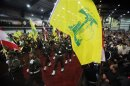Lebanon's Hezbollah members carry Hezbollah and Lebanese flags as they parade during a rally marking the party's Martyrs Day in Beirut
