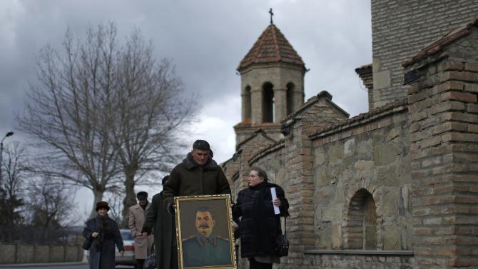 A man carries a portrait of Soviet dictator Josef Stalin on the anniversary of Stalin's death in his hometown Gori