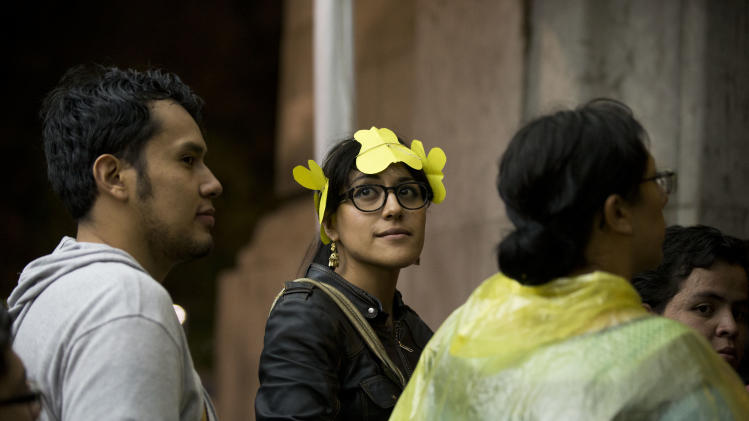 "EXPLAINS YELLOW BUTTERFLIES A young woman wears a headband of yellow paper butterflies as she waits to enter an homage for Colombian Nobel Literature laureate Gabriel Garcia Marquez at the Palace of Fine Arts in Mexico City, Monday, April 21, 2014. Garcia Marquez, known throughout Latin American and much of the world simply as ""Gabo,"" lived in Mexico for decades and wrote some of his best-known works here, included the renowned ""100 Years of Solitude."" He died Thursday in Mexico City at age 87. In One Hundred Years of Solitude, clouds of yellow butterflies precede a forbidden lover's arrival. (AP Photo/Rebecca Blackwell)"