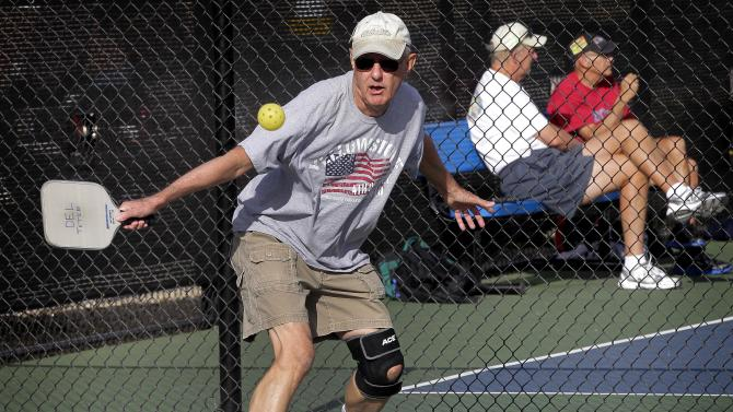 In this Monday, Dec. 3, 2012 photo, Del Teter competes in a game of pickleball at Sun City West senior community in Surprise, Ariz. A hybrid of tennis, badminton and table tennis, pickleball is played on a court a quarter the size of a tennis court, There's usually four players, two each side on a team, playing over a net slightly lower than in tennis, using rackets that look like a beefed-up version of a beach paddleball paddle to hit a whiffle ball that's slightly harder than the play-in-the streets variety.  (AP Photo/Matt York)