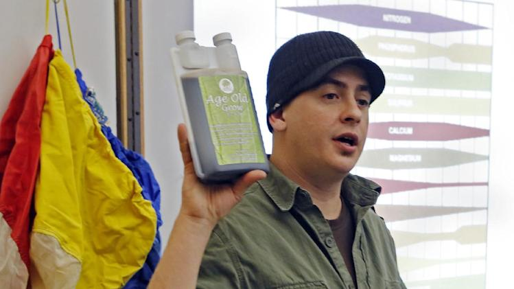 "In this photo taken on Saturday, Feb. 9, 2013, Instructor Ted Smith holds up a chemical that is recommended in growing marijuana during the first class at THC University in Denver. Smith told the first-time marijuana growers that chemical fertilizers work so quickly that some are called ""bud rocket."" (AP Photo/Ed Andrieski)"