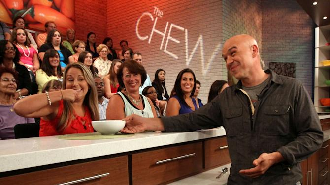 """This Friday, Aug. 26, 2011 photo shows Iron Chef Michael Symon, co-host of ABC's """"The Chew"""", right, as he runs through a tasting segment with members of the audience during a rehearsal for the show in New York. Can some of food and style TV's biggest stars help ABC soap fans get over cancellation of their favorite stories? The network's counting on it for """"The Chew.""""     (AP Photo/Tina Fineberg)"""