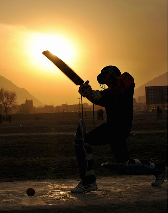 An Afghan boy plays cricket on the groun
