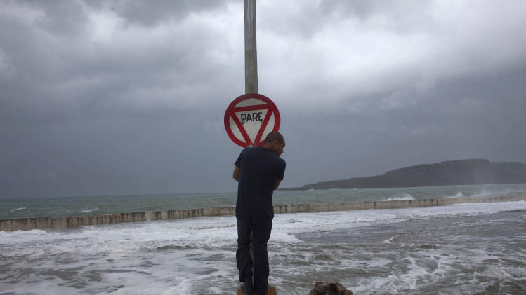 FILE - In this Aug. 25, 2012 file photo, a man stands on a post with a stop sign as waves push over a seawall during the passage of Tropical Storm Isaac in Baracoa, Cuba. In 2012 many of the warnings scientists have made about global warming went from dry studies in scientific journals to real-life experience. (AP Photo/Ramon Espinosa, File)