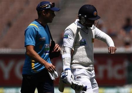 Sri Lanka's Sangakkara looks at his injured finger as he walks off the ground with a team trainer retired hurt during the third day of the second cricket test against Australia at the Melbourne Cricke