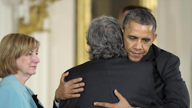 FILE – In this February 15, 2013, file photo President Barack Obama hugs Gilles Rousseau, father of slain Sandy Hook Elementary School teacher Lauren Rousseau, as her mother Terry Rousseau, watches at left during a White House ceremony in Washington to posthumously honor their daughter with the 2012 Presidential Citizens Medal. Families of the school shooting victims are making regular appearances with President Barack Obama and walking the halls of Congress to advocate for stricter gun regulations. They helped push through the nation's most restrictive firearms law in Connecticut this April. (AP Photo/Susan Walsh)