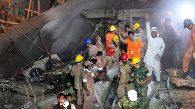 Rescue workers call for help while fire fighters, center, hose out a fire which broke out in a garment factory building which collapsed Wednesday in Savar, near Dhaka, Bangladesh, Sunday April 28, 2013. A fire broke out late Sunday in the wreckage of the garment factory that collapsed last week in Bangladesh, with smoke pouring from the piles of shattered concrete and some of the rescue efforts forced to stop. The fire came four days after the collapse, as rescuers were trying to free a woman they found trapped in the rubble.(AP Photo/Wong Maye-E)
