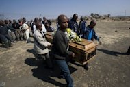 "A group of men carry the coffin on August 31, 2012 of one of the striking miners killed by police on August 16, at an informal settlement near the Lonmin mine in Marikana, South Africa. South African police expressed their ""deep regret"" over the shooting deaths of 34 miners and acknowledged that the force's response may have been disproportionate, in evidence before the Marikana inquiry on Monday"