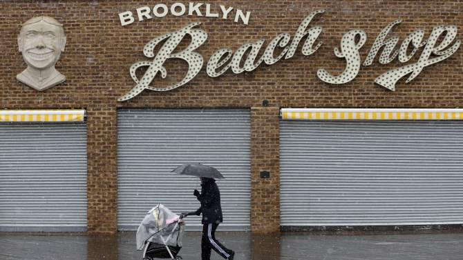 A pedestrian and a baby try to keep the snow off while walking along the Coney Island boardwalk in New York, Monday, March 25, 2013. A wide-ranging storm is hitting the East Coast after blanketing the Midwest and burying thoughts of springtime weather under a blanket of heavy wet snow and slush, though less snow was predicted to fall as the storm moves eastward. (AP Photo/Seth Wenig)