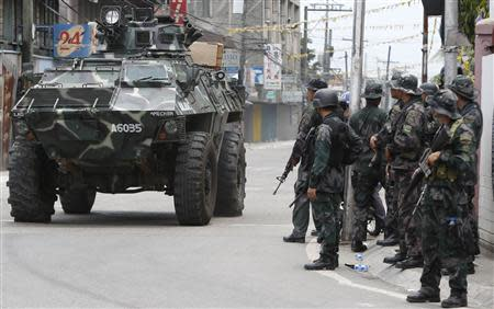 An armoured vehicle drives past government soldiers for another offensive against the Muslim rebels of Moro National Liberation Front (MNLF) positions in Zamboanga city