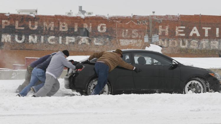 Motorist attempt to push a car back on the road in Wichita, Kans. Thursday, Feb 21, 2013.  Numerous cars and trucks were stuck or off the road as nearly a foot of snow fell across the area. Kansas was the epicenter of the winter storm, with parts of Wichita buried under 13 inches of still-falling snow, but winter storm warnings stretched eastern Colorado through Illinois. (AP Photo/The Wichita Eagle, Bo Rader)