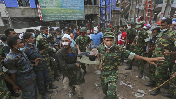 A Bangladeshi garment worker who was pulled alive from the rubble is rushed on a stretcher at the site of a building that collapsed Wednesday in Savar, near Dhaka, Bangladesh, Friday, April 26, 2013. By Friday, the death toll reached at least 270 people as rescuers continued to search for injured and missing, after a huge section of an eight-story building that housed several garment factories splintered into a pile of concrete. (AP Photo/Kevin Frayer)