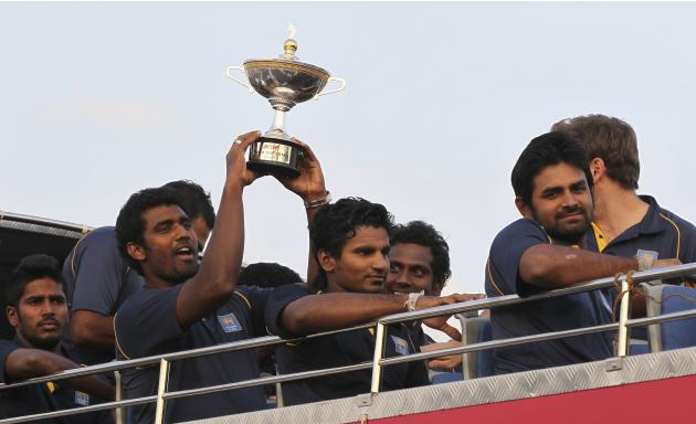 Sri Lankan cricket team members from left, Chathuranga De Silva, Thisara Perera, holding cup, Kusal Janith Perera, captain Angelo Mathews, and Lahiru Thirimanne travel in an open bus as they return fr