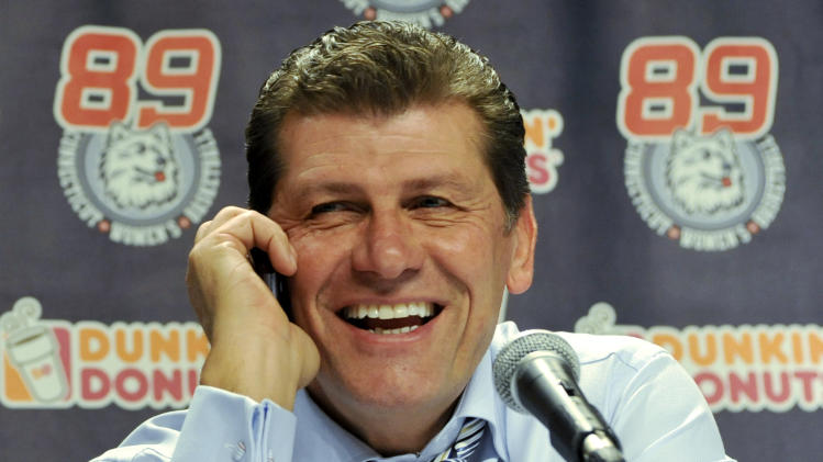 Connecticut coach Geno Auriemma takes a congratulatory phone call from President Barack Obama, during a news conference after Connecticut beat Florida State 93-62 in an NCAA college basketball game in Hartford, Conn., Tuesday, Dec. 21, 2010. Connecticut set an NCAA record with 89 consecutive wins . (AP Photo/Jessica Hill)