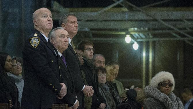 From left, NYPD's Chief of Department James O'Neill, NYPD Commissioner Bill Bratton, and New York City Mayor Bill de Blasio, attend mass at St. Patrick's Cathedral, Sunday, Dec. 21, 2014, in New York. The previous day an armed man walked up to two New York Police Department officers sitting inside a patrol car and opened fire, killing both before running into a nearby subway station and committing suicide, police said. (AP Photo/John Minchillo)