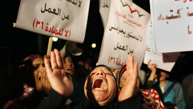 "An Egyptian woman chants slogans criticizing the Islamist-dominated constitutional assembly while fellow protesters carry placards that read in Arabic ""no for the constitution that will deprive me from working, no for article 36,"" during a protest in Cairo, Egypt, Tuesday, Oct. 2, 2012. Islamists are seeking to enshrine in Egypt's new constitution a number of articles that secularists and liberals fear would bring theocratic rule and severely set back civil liberties, including provisions empowering clerics to review laws and restricting women's rights. (AP Photo/Nasser Nasser)"