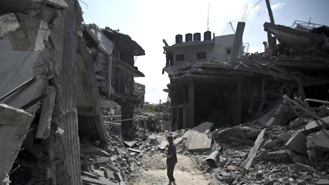 A Palestinian man stands amid the rubble of buildings following an Israeli military strike in the Jabalia refugee camp, in the northern Gaza Strip, on August 9, 2014