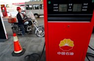A Chinese man waits to fuel up his motorbike at a petrol station in Suining, southwest China&#39;s Sichuan province in March 2012. China&#39;s economic planning ministry said it will lower benchmark retail prices of gasoline and diesel by 530 yuan ($84) and 510 yuan per tonne respectively
