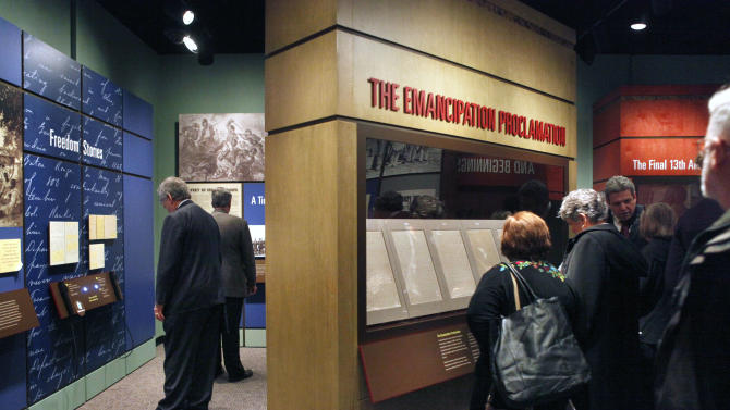 """FILE - This Nov 4, 2010 file photo shows National Archives visitors looking at a display of President Abraham Lincoln's Emancipation Proclamation at the National Archives in Washington. As New Year's Day approached 150 years ago, all eyes were on Lincoln in expectation of what he warned 100 days earlier would be coming _ his final proclamation declaring all slaves in states rebelling against the Union to be """"forever free."""" A tradition began on Dec. 31, 1862, as many black churches held Watch Night services, awaiting word that Lincoln's Emancipation Proclamation would take effect as the country was in the midst of a bloody Civil War. Later, congregations listened as the president's historic words were read aloud.  (AP Photo/Jacquelyn Martin, File)"""