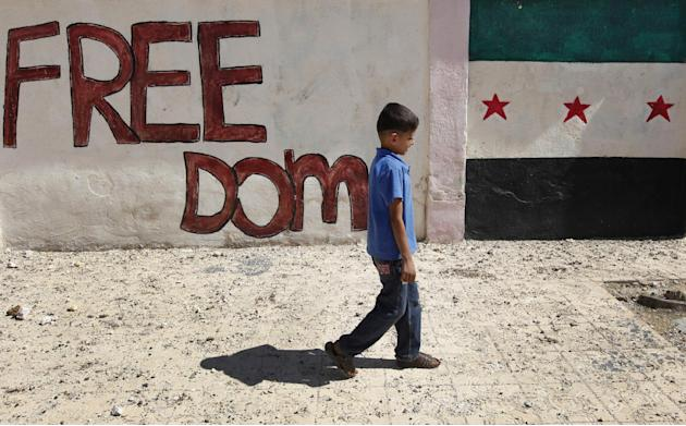A Syrian boy walks in front of wall painted with colors of the Syrian revolutionary flag, right, in Marea village, on the outskirts of Aleppo, Syria, Sunday Sept. 23, 2012. Syria's bloody 18-month con