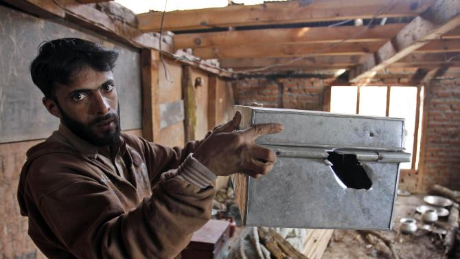 """Kashmiri villager Rafiq Ahamad displays a box allegedly damaged by firing from the Pakistan side of the border, inside his home near the Line of Control, the line that divides Kashmir between India and Pakistan, in Churunda village, about 150 Kilometers (94 miles) northwest of Srinagar, India, Tuesday, Jan. 15, 2013. India's relations with archrival Pakistan """"cannot be business as usual"""" in the wake of a spate of attacks in Kashmir, Prime Minister Manmohan Singh said Tuesday in a statement that threatens to ratchet up tensions in the wake of the Himalayan violence. A series of tit-for-tat attacks, including the beheading of an Indian soldier, across the LOC that divides the Himalayan region has killed two Pakistani and two Indian soldiers over the past 10 days. (AP Photo/Mukhtar Khan)"""